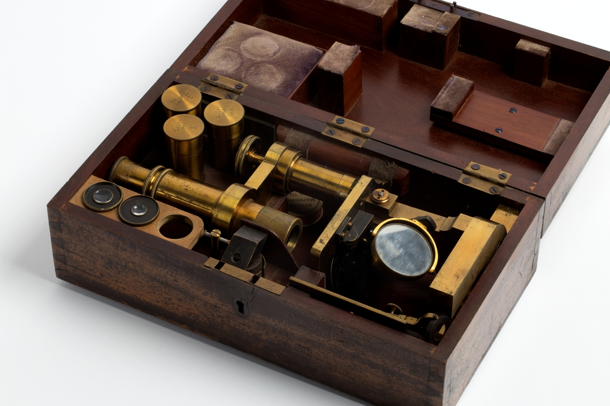 Mikroskop i kasse med hengslet lokk. Lås for nøkkelbruk. Nøkkel mangler. Kassen er innvendig pålimt/påskrudd støtteklosser for delene. Klossene er kantet med fløyel. Alle tilhørende deler til mikroskopet er merket med A - M. Synes å være omtrent fullstendig. I tillegg et stk. kartong påskrevet styrkeforklaringer på de ulike okularer i kassen.