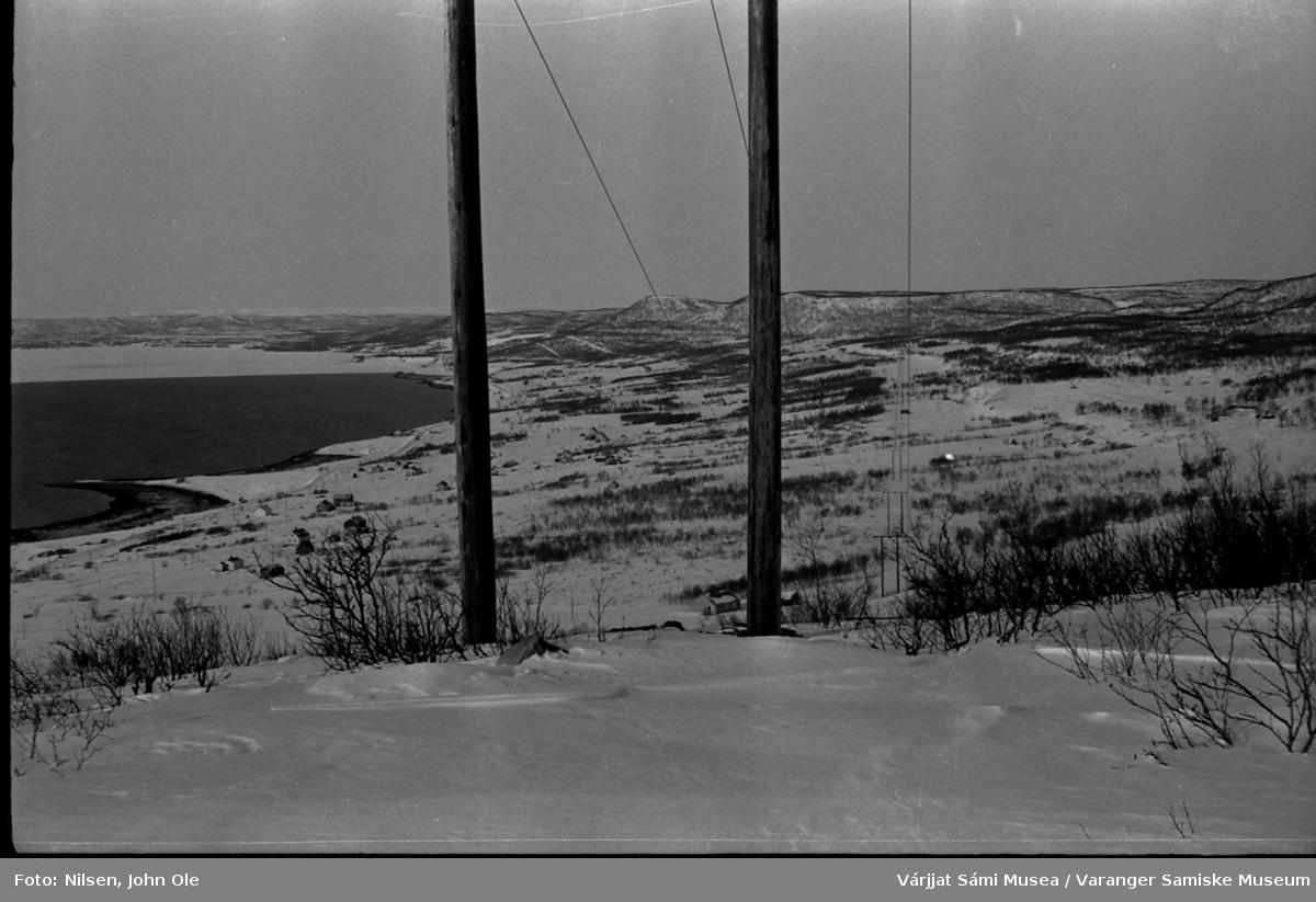 Vinterbilde  tatt fra Abelsborgfjellet med flott utsikt innover Meskfjorden (indre del av Varangerfjorden). Kanten på fjordisen har lagt seg ved Meskelv. 1967