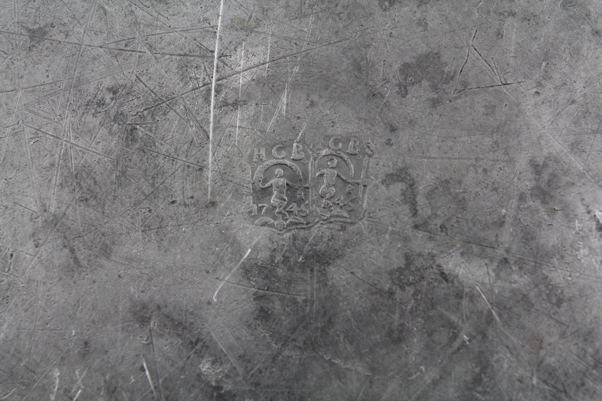 Sirkelrund, ganske sterkt forsenket midte prydet med gravert sirkellinje, horisontal kant med gravert linje ved randen.Baksiden stemplet. Innrissede bokstaver på kanten.