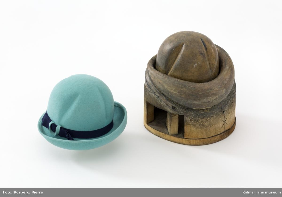 KLM 29987. Hatt, nackhatt. Ljusblå nackhatt tillverkad av filt med ett mörkblått ripsband runt nedre delen av kullen. Nackhatten har en veckad kulle och ett uppvikt brätte snett framtill. I storlek 55.