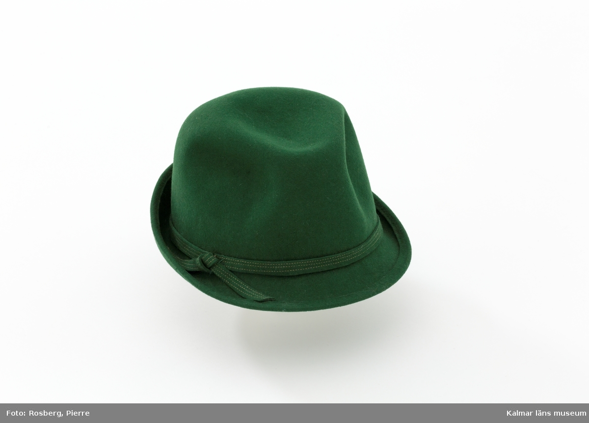 KLM 30017. Hatt, damhatt, tyrolerhatt. Mörkgrön tyrolerhatt i herrhattsmodell. Runt nedre delen av kullen löper ett mörkgrönt filtband. Hatten har uppvikt brätte baktill och sluttande brätte framtill. Veckad kulle. Hatten är i storlek 54 och form 807.