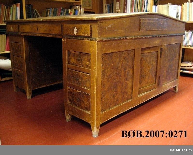 Dobbelt skrivebord, der ein sit mot kvarandre. Skrivebordet er i tre delar. det er to skuffe/skapseksonar og toppseksjon. Skriveflatene er skråstilt og inneheld skuffar.