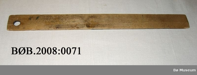 Form: Rektangel. Den eine langsida er skrådd og det er eit rundt hol i linjalen.