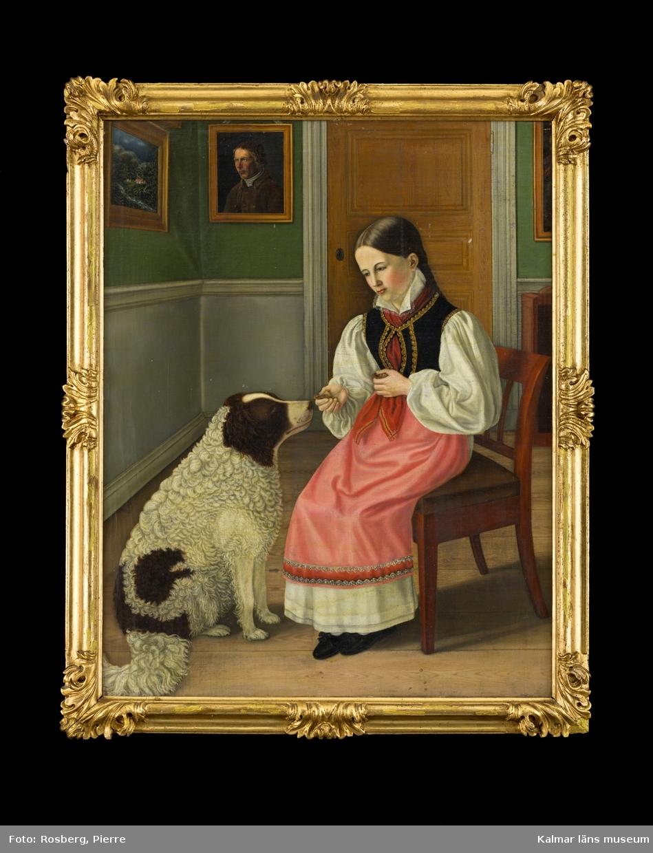 Interiörbild, i motivet centrum en flick som sitter på en stol och matar en stor lurvig hund. Hon sitter i ett rum där man ser ett hörn av rummet med dörr, vägg med grön tapet, grå bröstning, samt tavlor på väggarna. Trägolv.