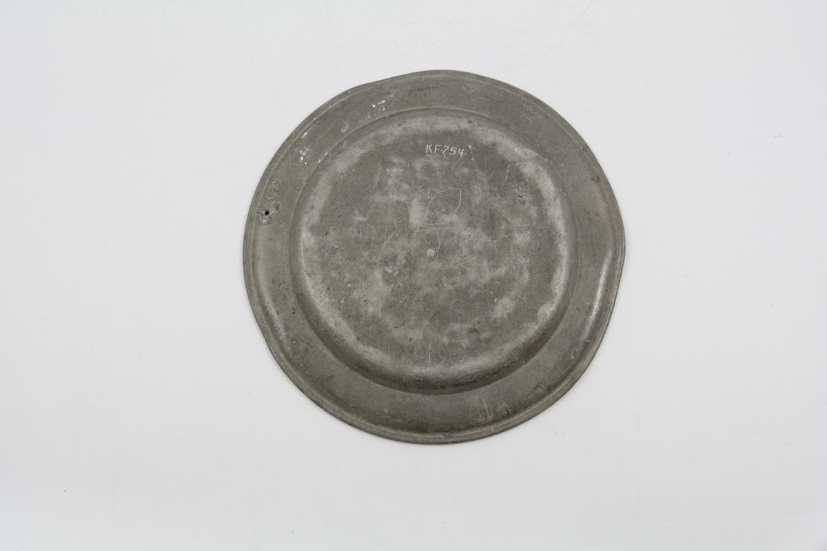 Flat, tinn, sirkelrund, horisontal kant med lett oppbøyet rand prydet med gravert linje. Baksiden stemplet to ganger. Inngraveringer på kanten.