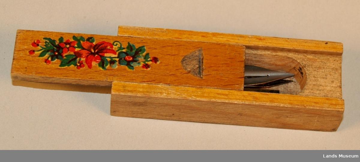 Pennesplittholder med tre pennesplitter. Lokket kan skyvast av. Dekorert med eit blomstermotiv på lokket.