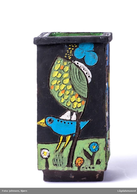 Motivet består av diverse fuler, blomster og ett hus.