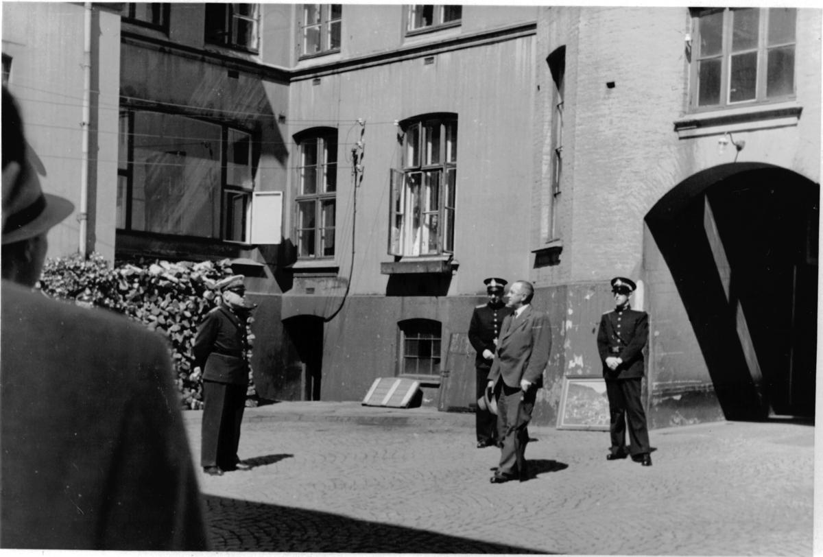 En seremoni, overrekkelse av blomster, i bakgården til politistasjonen (ant). Mulig en avskjedsseremoni.