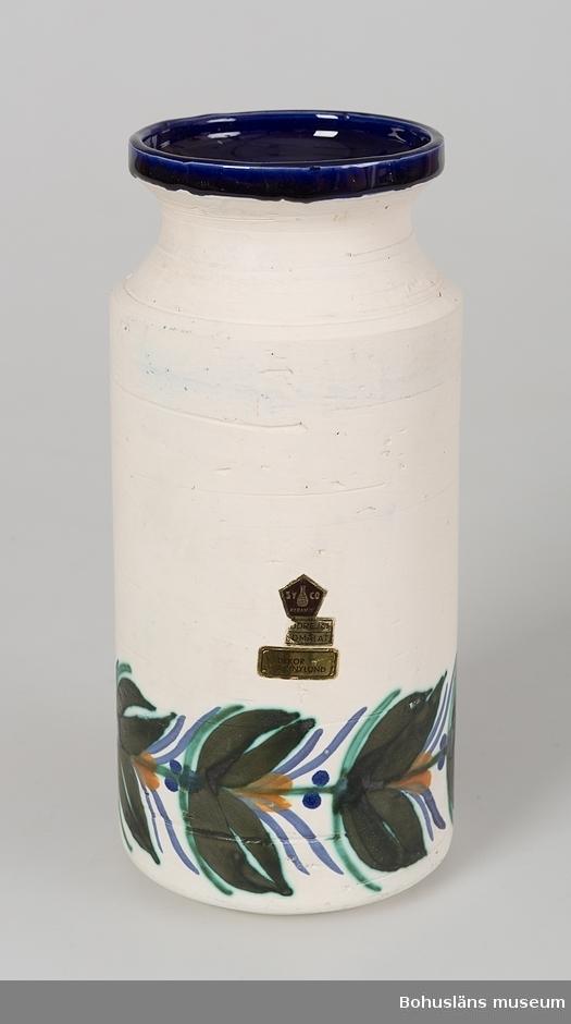 """Cylinderformad, konkavt mynningsparti. Vit, matt glasyr. Nedtill runt vasen är den handmålad med stiliserad bård i mörkgrönt, ljusgrönt, blått och orange.  Invändigt täckt med blank, blå glasyr. På sidan fastklistrad femkantigt fabriksmärke av papper för """"SYCO - keramik"""" med texten: """"Handdrejat, handmålat"""" samt rektangulärt märke """"A.Nylund"""". Under botten märkt i blått: """"AN"""".  Av givaren inköpt på Uddevalla Auktionskammare."""