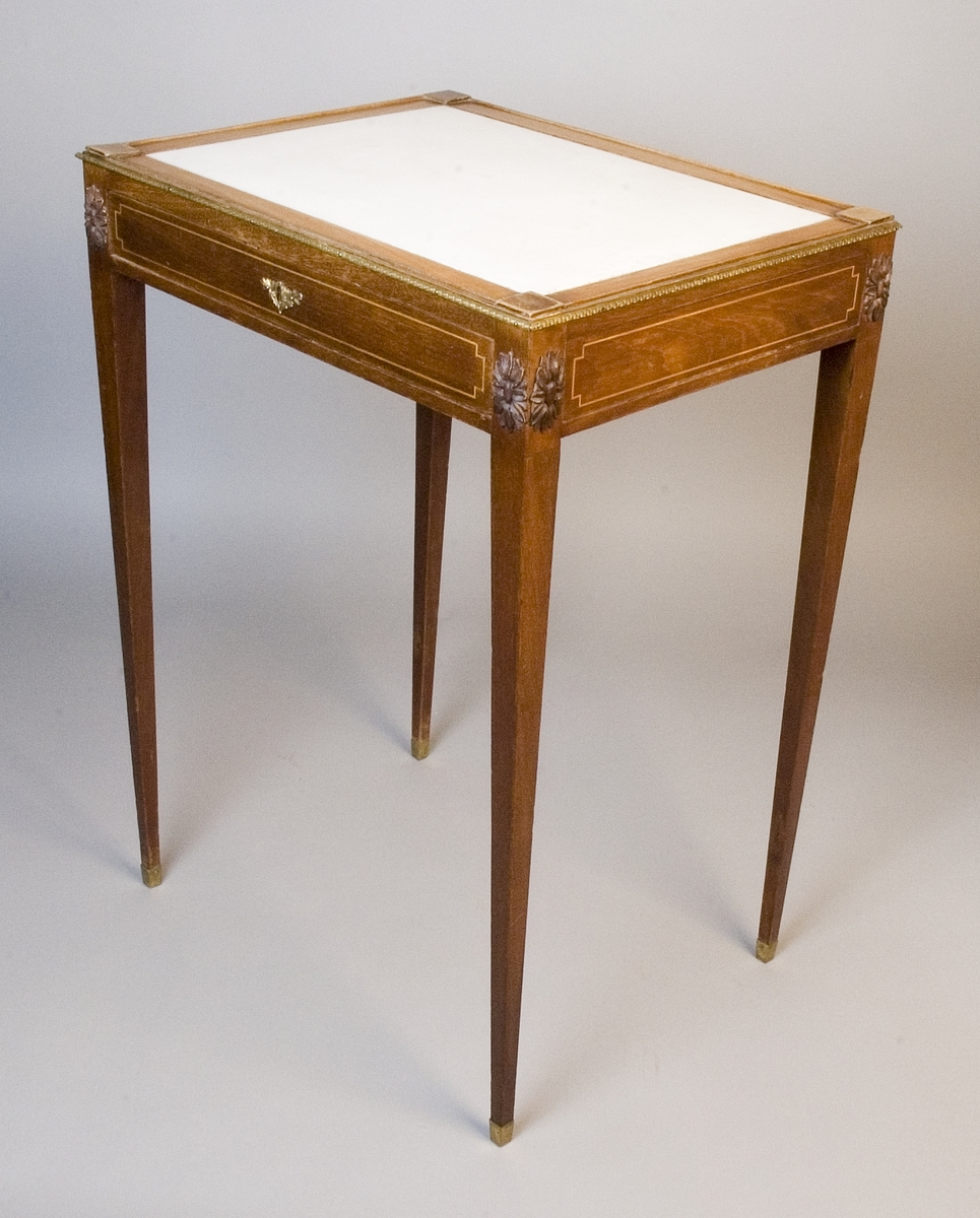 Rektangulärt sybord av mahogny med en låda och skiva av vit marmor. Raka sarger med inläggning av enkel geometrisk bård, nyckelskylt av mässing och hörnbeslag i form av påsatta snidade fleuroner av trä. Raka avsmalnande ben med fothylsor av mässing. Runt kanterna en tunn mässingslist med lagerstav. Skivan infälld i ram av trä med utanpåliggande kvadrater i hörnen.