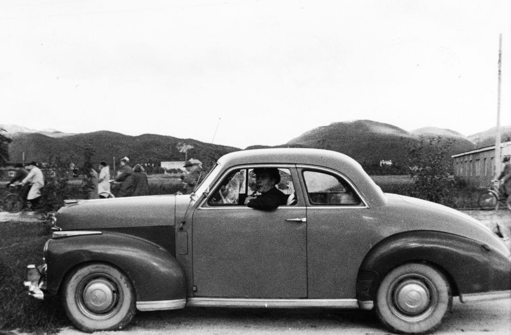 Landskap. Bodø. En bil av merket Studebaker står parkert. En mann sitter i førersetet. I bakgrunnen Bodøfjellene med Junkeren høyest.