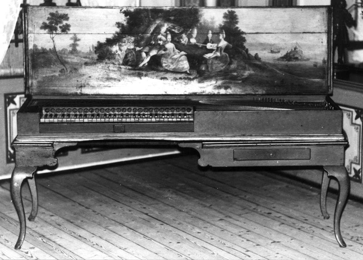 Omfang: FF - f''' (5 oktaver). Flat, rektangulær kasse med løst understell på 4 svungne ben. Utvendig blåmalt med forgylte lister, skuff på høyre side. Kassens innvendige lister rødmalte, lokket forsynt med maleri: landskapsmotiv, i forgrunnen en gruppe rokokkokledte mennesker, 3 menn, spillende sekkepipe, tverrfløyte og gitar, 3 kvinner, to av dem holdende notehefter, og 2 små barn (piker). Til høyre på bildet sjø med holme, hvor man ser en borg. Fra et av tårnene vaier det danske flagget. På sjøen er også en båt.  Tastebelegg: undertastene elfenben, sortmalte overtaster. Tokorig.  Venstre side av klangbunnen avdempet ved røde filtbånd.  På tastene C og d' befinner seg polster (for opprinelig pedal?).