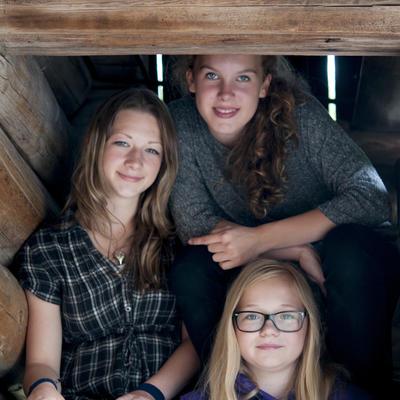 Tre unge jenter sitter i trapp i Friluftsmuseet