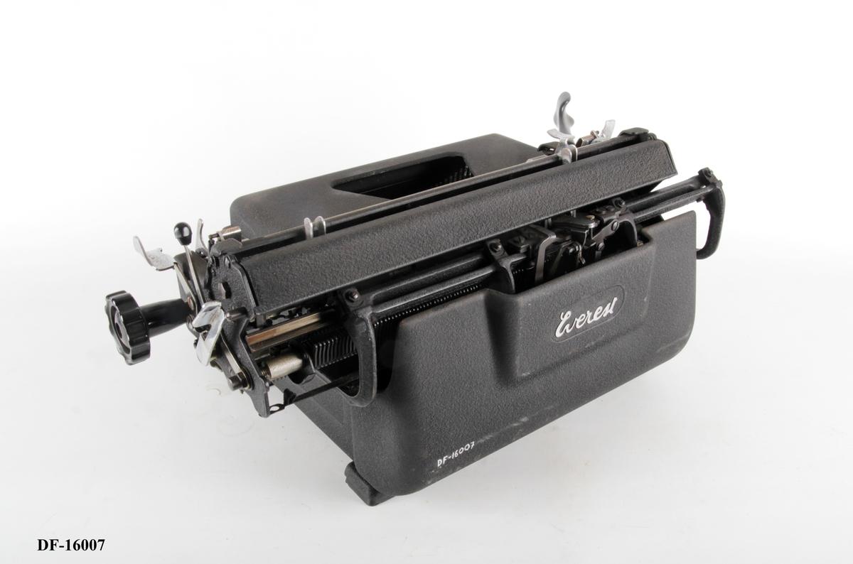 Manuell skrivemaskin med skrivevalse og fargebånd med to farger (svart og rød).