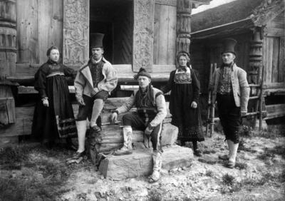 Kvinner og menn i drakter foran loftet fra Rofshus. Foto/Photo