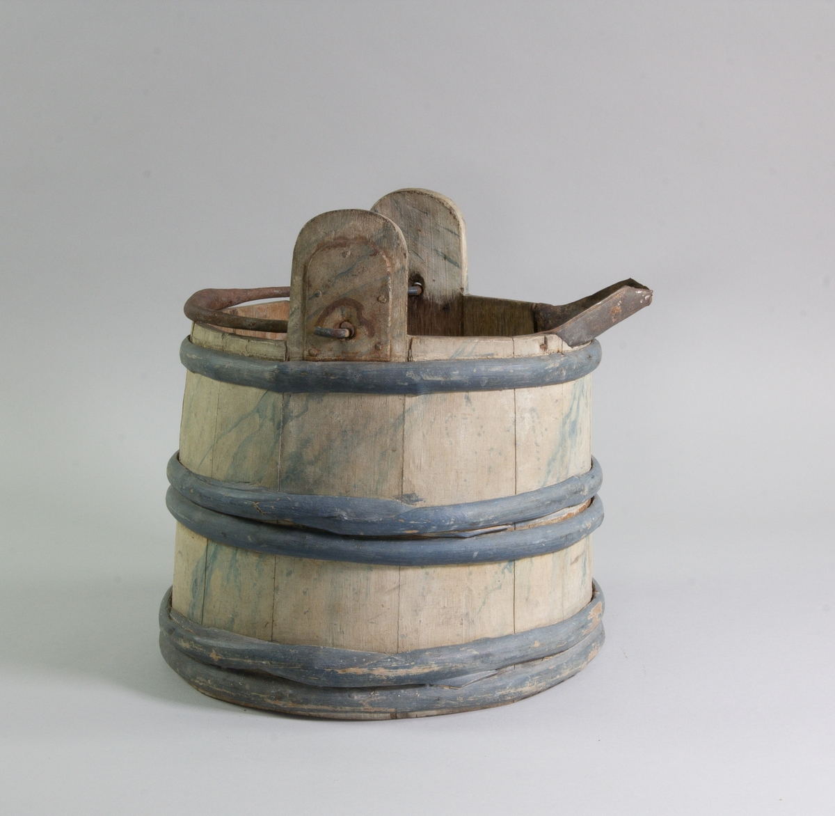 Laggkärl av trä med tre sammanhållande band av vidjor av en. Två av laggarna övergår i uppstående, järnskodda fästen för bärhandtag av järn. Påspikad uthällningspip av järnbleck. Bleknad blå marmorerad dekor, vidjorna blåmålade.