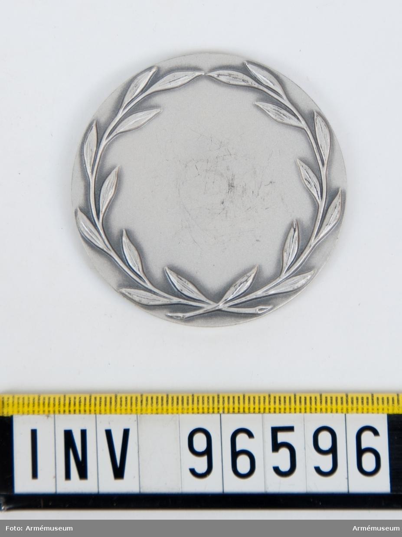 Medalj i silver för Norrlands artilleriregemente. Stans 27191, härdad 1961-09-01. Medalj, frånsida med stiliserade kvistar.