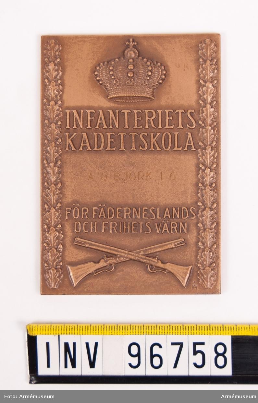 Plakett i brons för Infanteriets kadettskola. Samt kopia av brev med godkännande av plakettens ändring. Plakett upptagande kunglig krona samt krysslagda gevär flankerade av tvenne eklövslänkar, med inskr. INFANTERIETS KADETTSKOLA FÖR FÄDERNESLANDS OCH FRIHETS VÄRN, enligt modell av skulptör Åke Hammarberg. Stans nr 9216. Stans härdad 1950-06-15. Stans ändrad 1961-11-17.