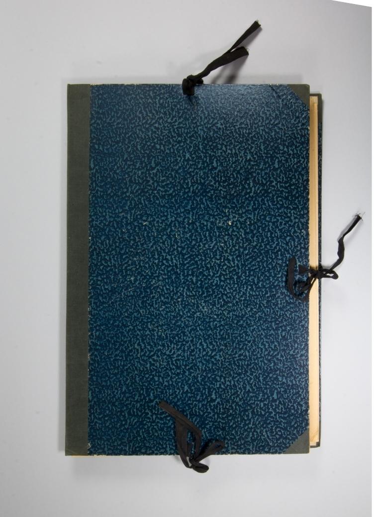 """Portfölj, stående rektangulär av papp med blåmarmorerat omslag. Knytband på tre sidor av svart bomullsband. Rygg av blå textil. Pärmarnas insidor har tryckt småblommigt mönster i grönt. Mellan pärmarna pappskivor och olika nummer av tidningen Svenska Dabladet 1911. Har ursprungligen innehållit skisser med mera. Lös etikett med text """"Bibelpl, Sorgen vid Kristi Kors, Dopet"""" och avser tidigare innehåll."""