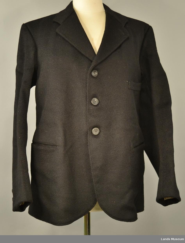 Lukket med tre knapper. Tre lommer på utsida og ein på innsida. Klaff på innsida av dei to lommene nede på jakka. Ei påsydd hempe i nakken.