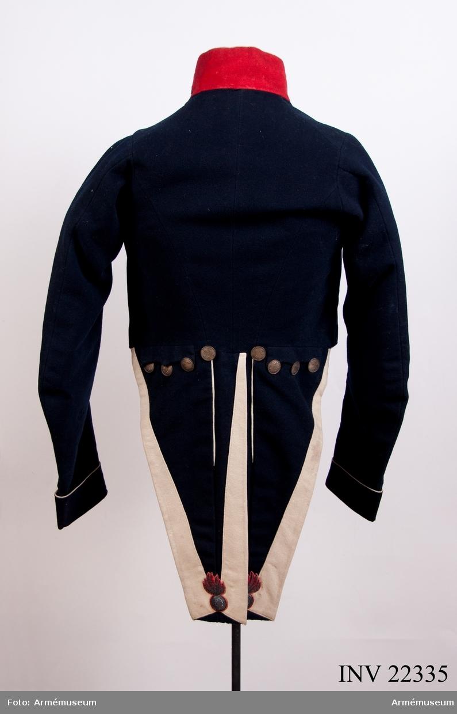 """Grupp C I. """"Burits av öfverste G. Nordenskjölds ss. fänrik i norska kriget 1809.""""  Gåva av överste G. Nordenskjölds dödsbo, Eksjö 1902-06-04. Mörkblå med röd, hög kragen med silvergalon på matta av rött kläde.  Vit passpoal framtill, nedtill runt ärmarnas uppslag och runt speglarna. Liten bandsölja för axelklaffarna eller epåletten på axlarna. Runt kragen en vit pesspoal. 7 stora flata knappar med tre kronor på räfflad bottten mitt fram. Silver. Fracken är fodrad med vitt kypertvävt tyg  som ser ut som vaxat linnetyg. Glättat."""