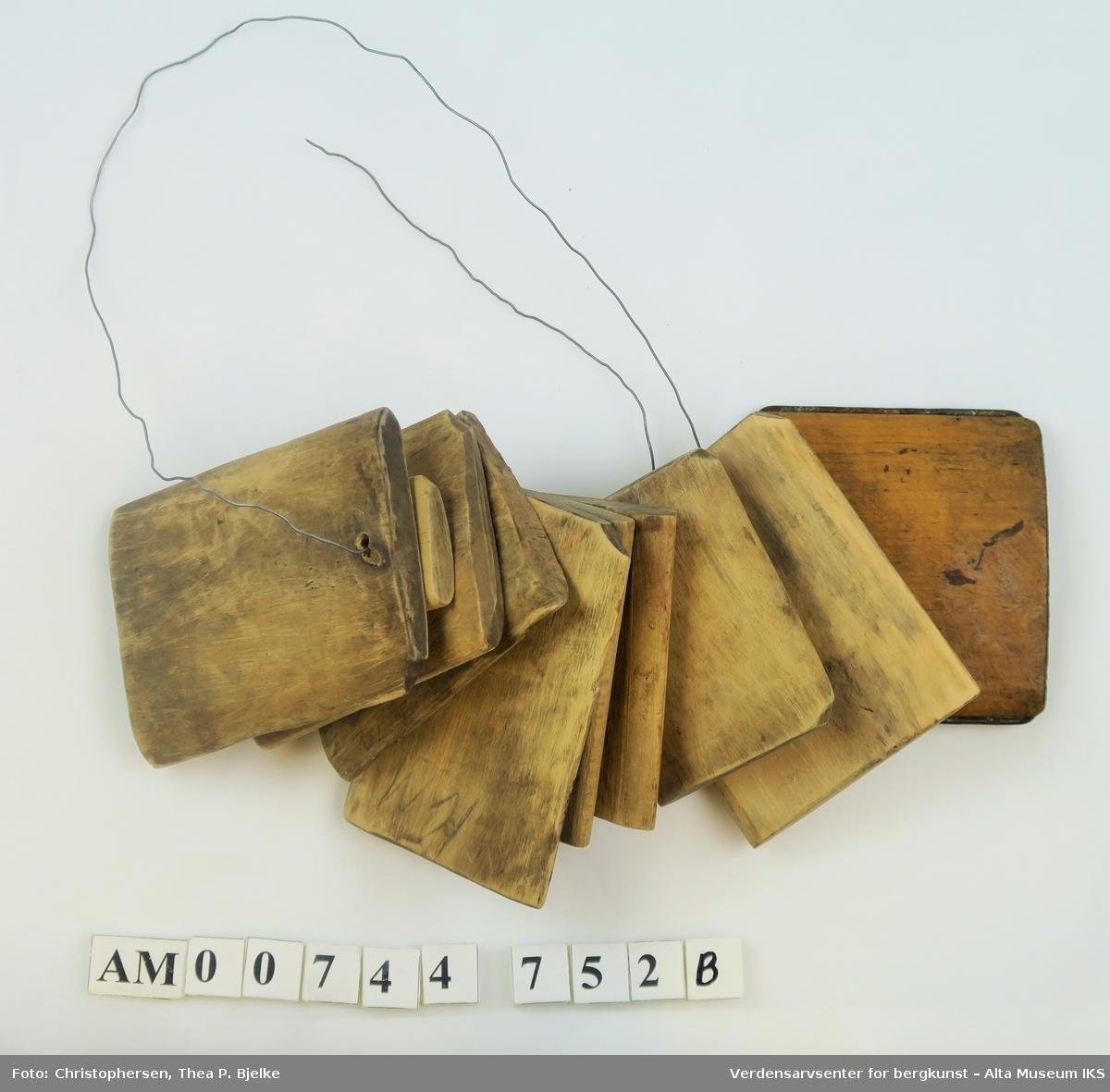 Liten, flat trekloss beskyttet med jernstreng i hver av kortsidene. Et hull er boret i den ene enden.