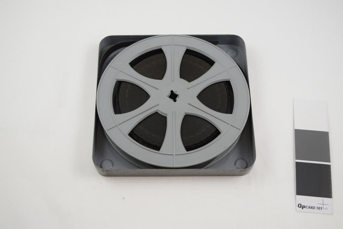 Filmrull i eske. Film på plastspole. Kvadratisk metalletui med avrundede hjørner, to løse deler: bunn og lokk.