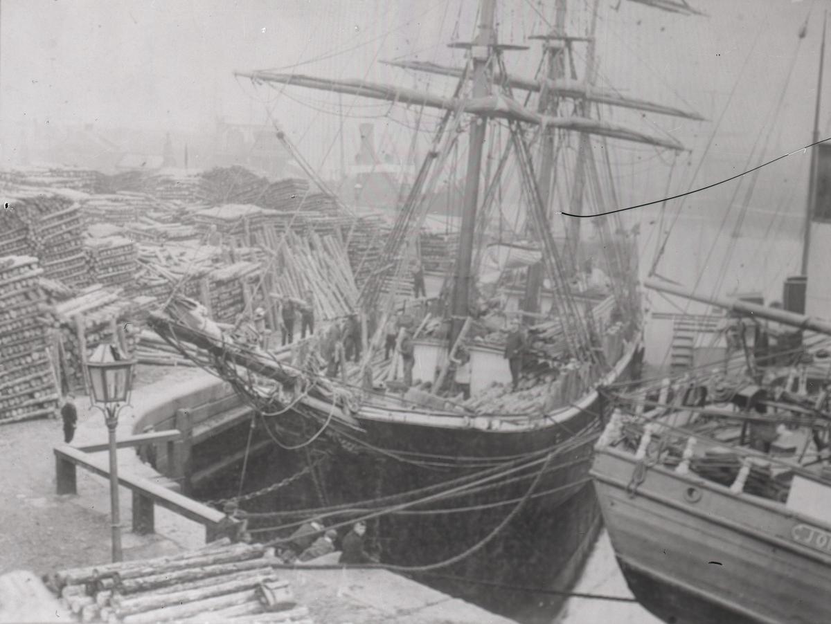Lastning av timmerstock på fartyg vid hamnen.
