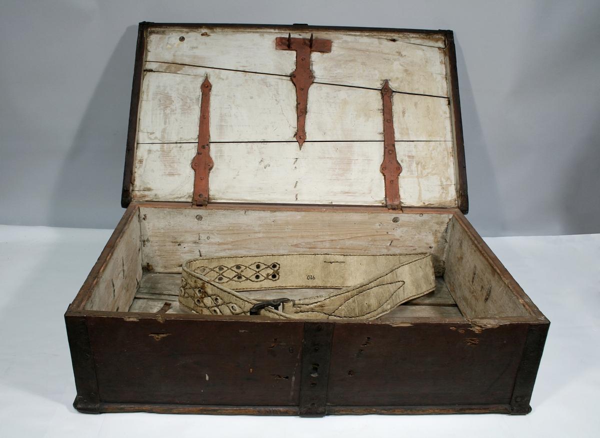 Brunrød trekiste med jernbeslag og jernhåndtak på begge kortsider. Kan låses med hengelås. Hvitmalt inni.