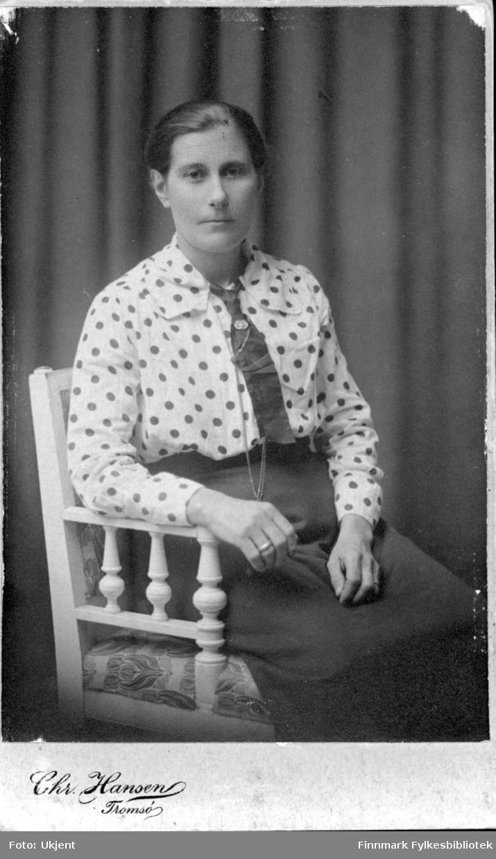 Et portrett av Amanda Mathisen. Hun er kledd i en prikkete skjorte med et skjørt. Hun har også på seg et slips dekorert med smykker. På sin høyre hånd har hun en ring. Hun sitter på en dekorativ stol.