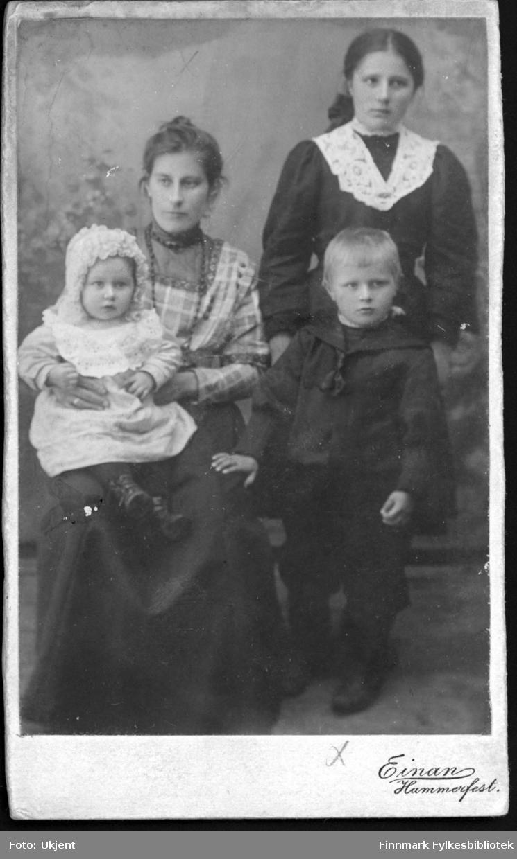 Et portrett av Amanda Mathisen med barna Magnhild (venstre) og Wilhelm (høyre). Amandas kusine Anna Dahl står bak den lille Wilhelm. Kvinnene har på seg kjoler, Amanda har et smykke rundt halsen. Magnhild har på seg en hette av noe slag og Wilhelm har en maritim - inspirert skjorte på seg.