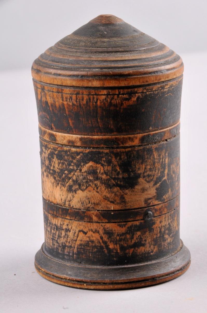 """Dreia trekrus med lok. Måla mørkt, nesten svart. Ein ser litt av treet gjennom målinga. Noko slitt langs kanten på loket. Dreia med riller til dekor, både på loket og sjølve huset. Ein liten """"sokkel"""" nederst, noko breiare enn resten. Trekvitt inni, truleg bruka til kaffi."""