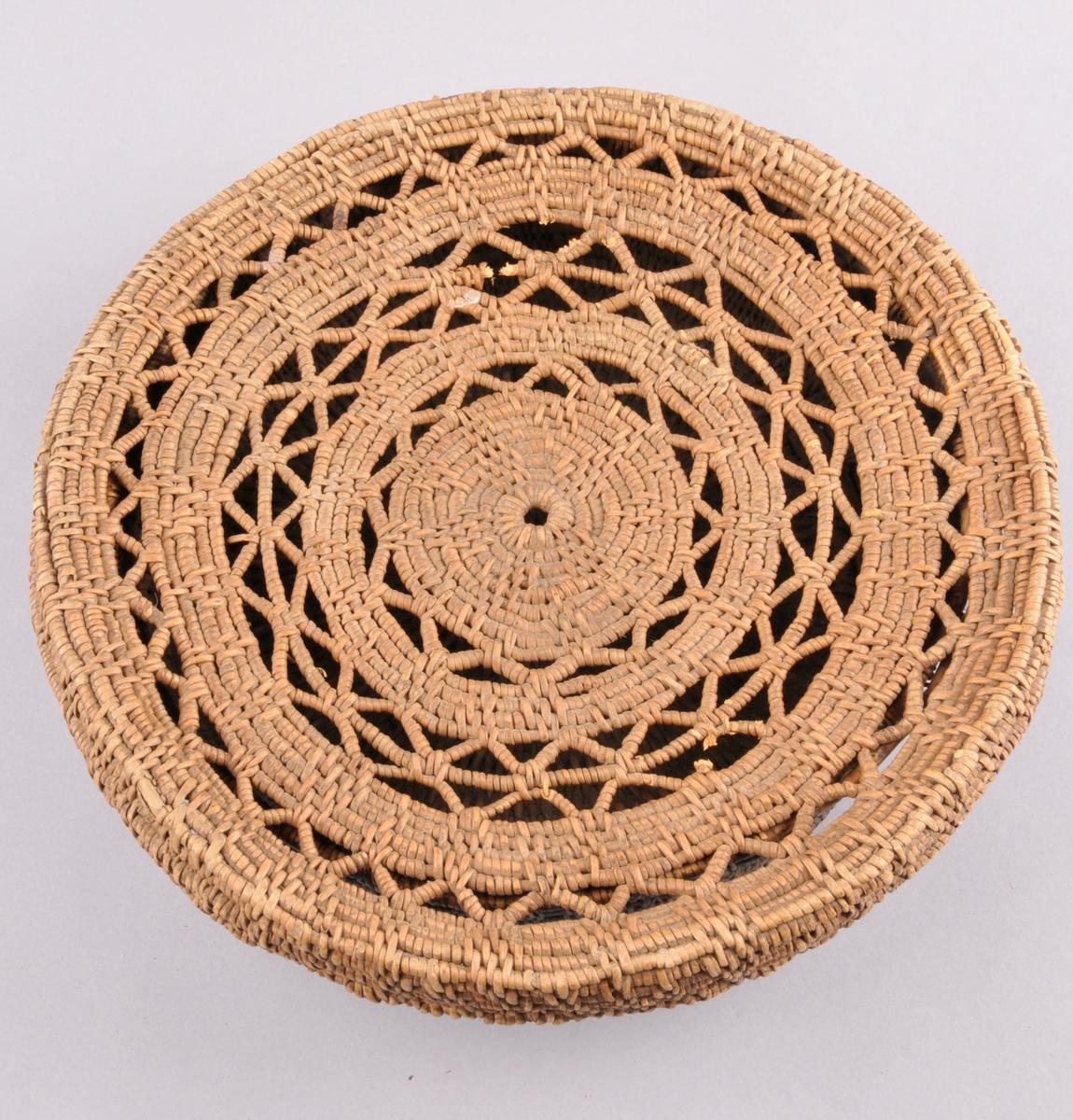 Tæge laga av bjørkerøtter. Med lok. Loket har sirkel/sol motiv, og sikksakk mønster. Trekantmønster på sjølve tæja. Loket er ein god del større og lysare enn resten ab tæga.