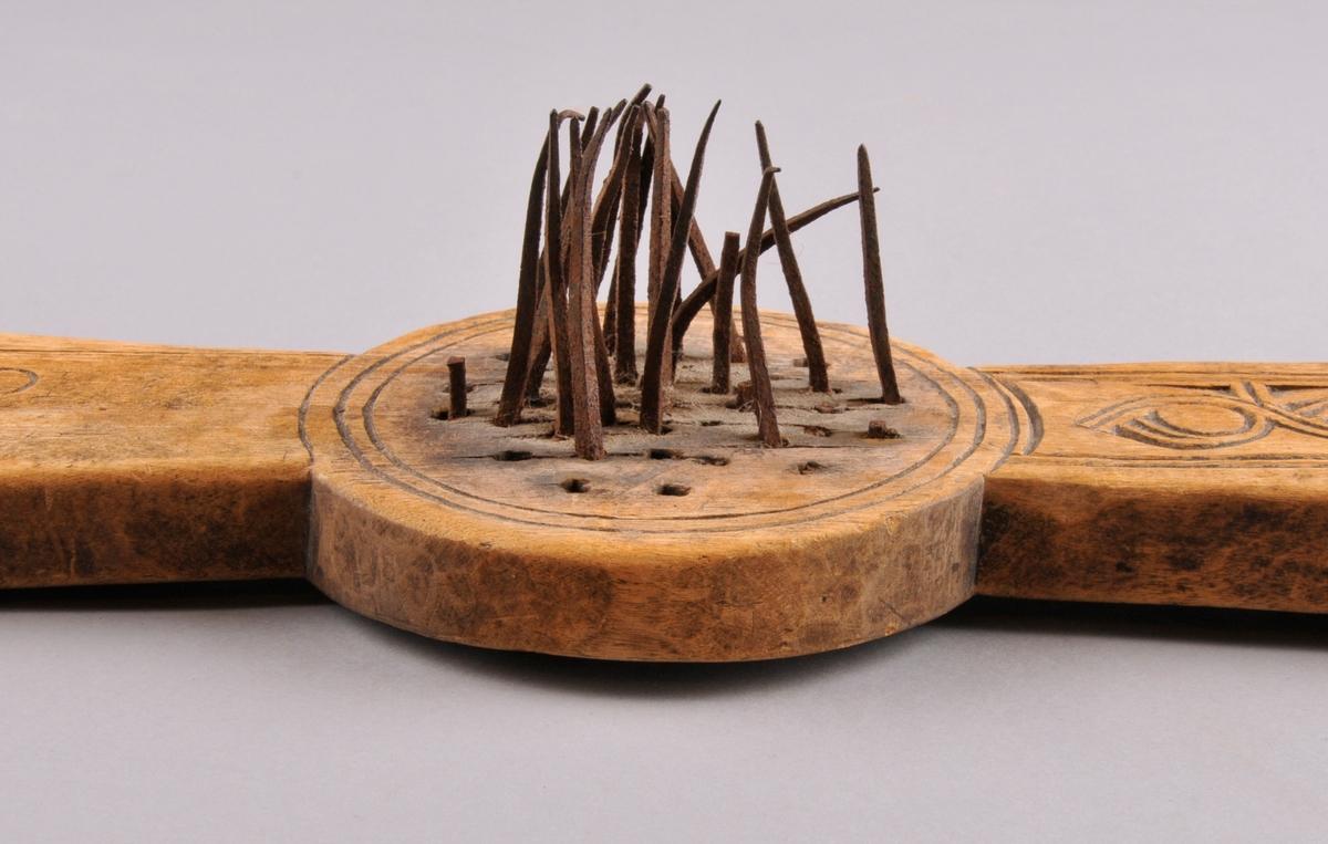 Linhekle med jarntindar spikra inn, fleire av dei manglar. Påsett jarnbeslag på kvart handtak. Dekorert med treskurd, innskrift.