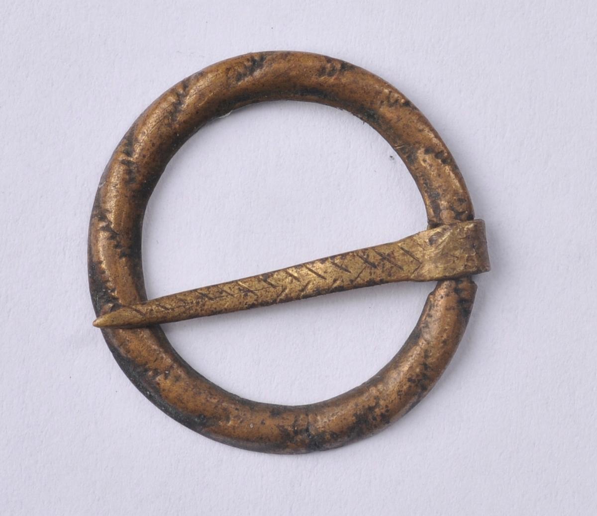 Lita sirkelforma sprette i messing. Sprettet har tein tvers over og er dekorert med skråstilde striper, slik at det kan sjå ut som om sprettet er sett saman av fletta trådar. Sprettet er støypt.