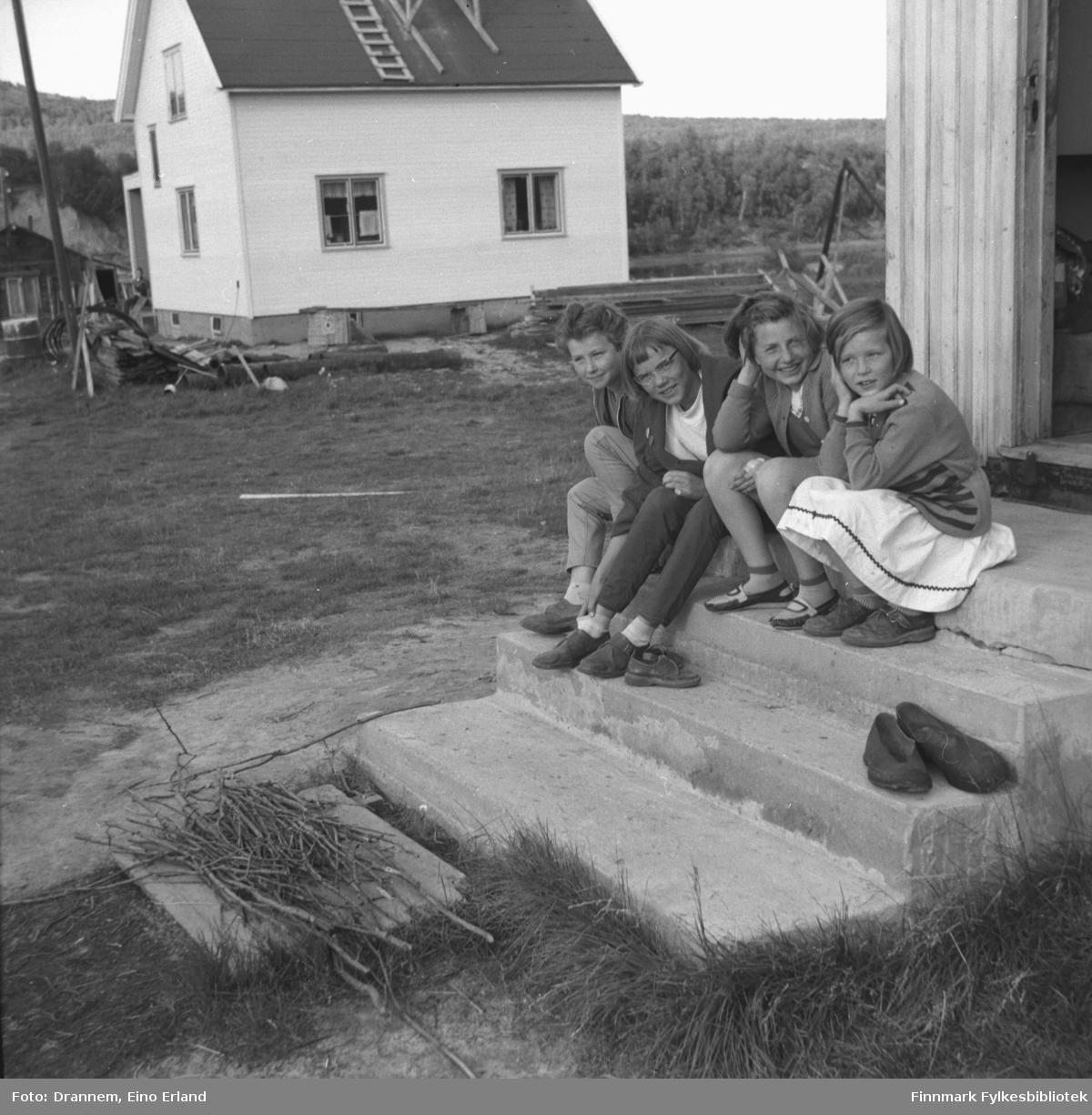Fire jenter sitter på en betongtrapp i Neiden. Jenta helt til venstre er Turid Karikoski, de andre er ukjente.