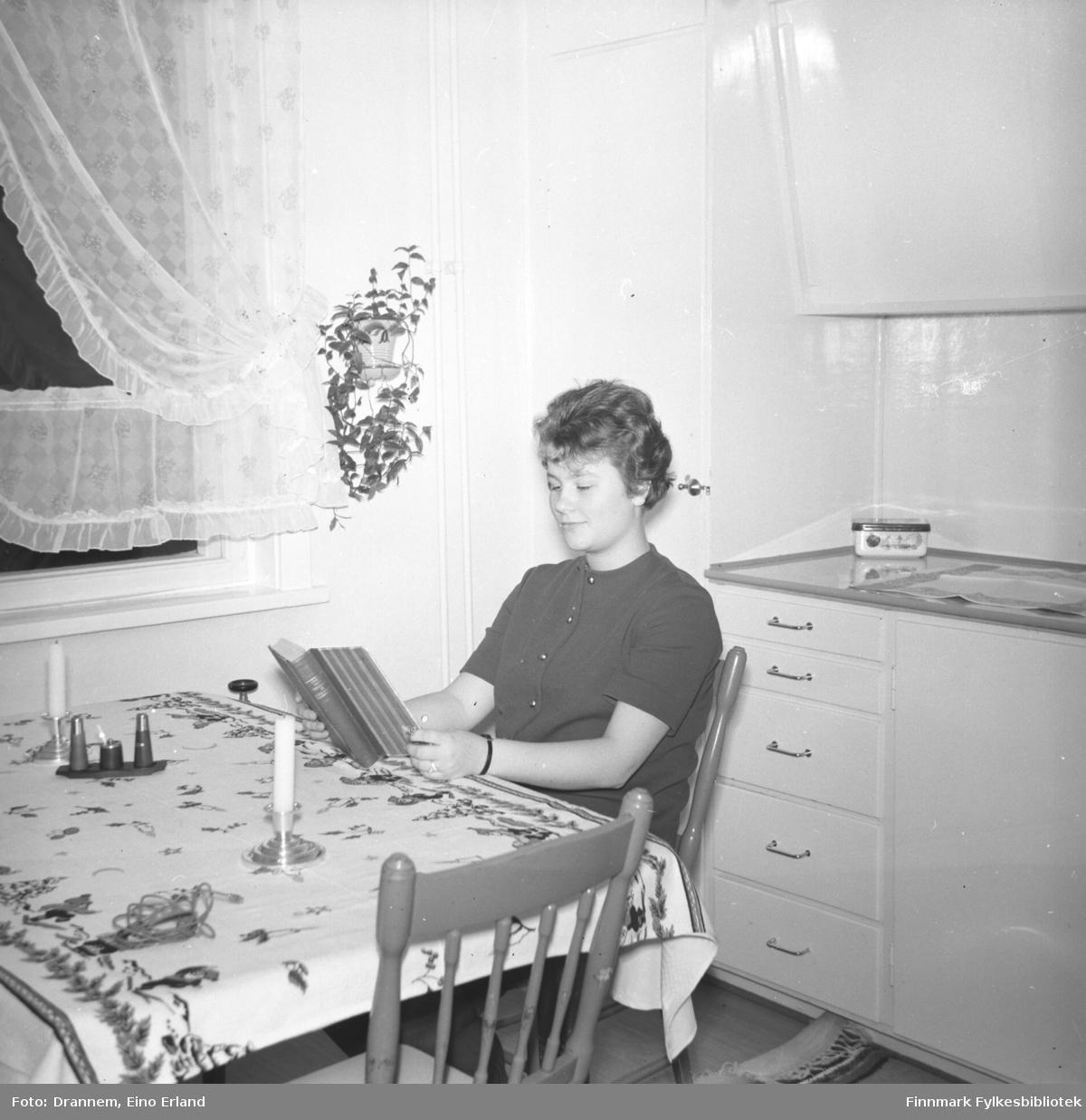 Turid Karikoski sitter og leser ved kjøkkenbordet hjemme i Hammerfest.