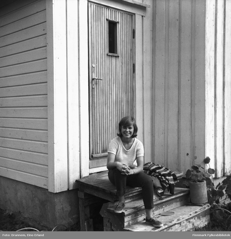 Marit Gabrielsen sitter på trappa foran en bolig i Neiden en sommerdag.