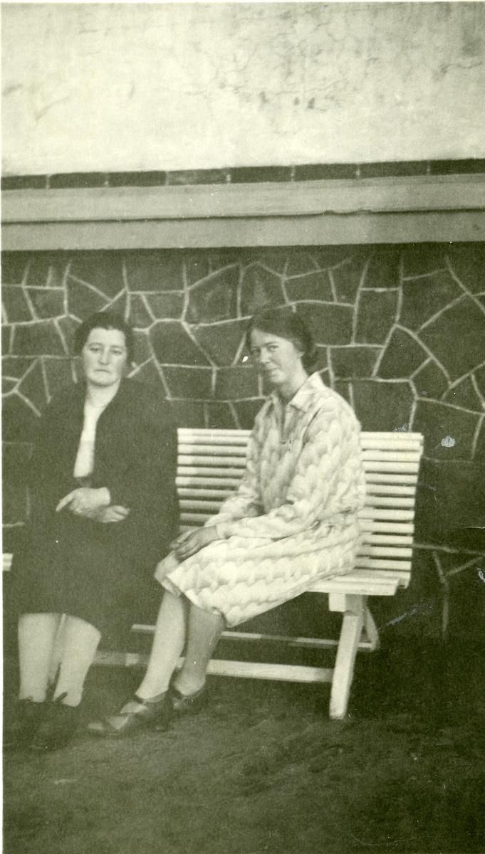 Portrett av to kvinner sittende på en benk.