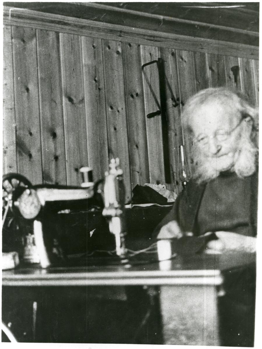 Portrett av skredder Gudbrand O. Skimten, sittende ved sin symaskin.