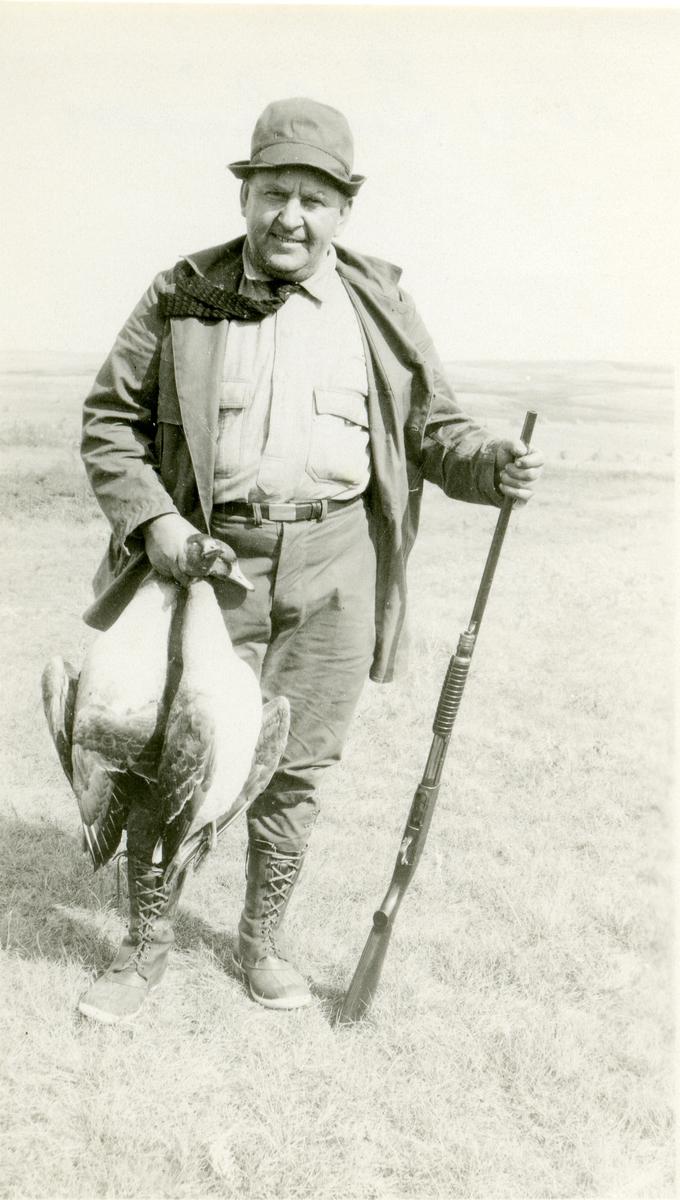 Mann i jaktklær med våpen. I hånda holder han jaktbytte, 2 fugler.