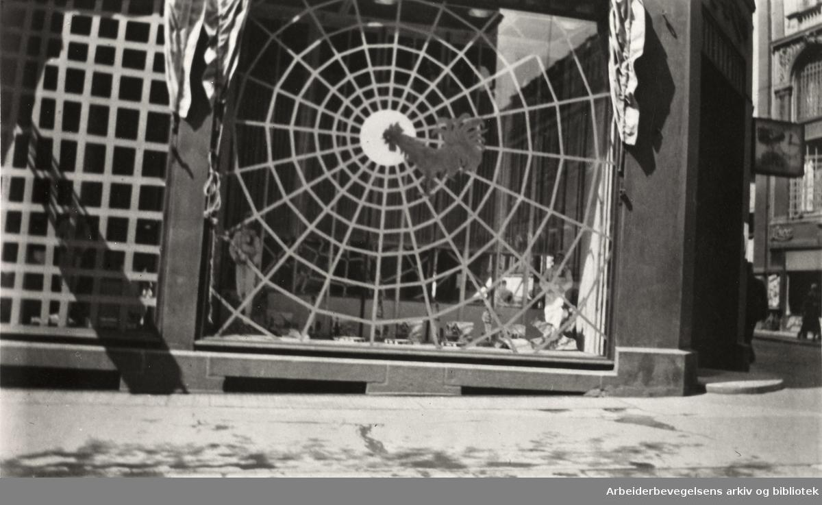 Ole M. Engelsens fotografier fra okkupasjonsårene i Oslo. Slik ble vindusrutene sikret for å hindre at glasset skulle splintres ved flyangrep..Sætre kjeksfabriks utsalg i Karl Johan gate 18, mai 1940.