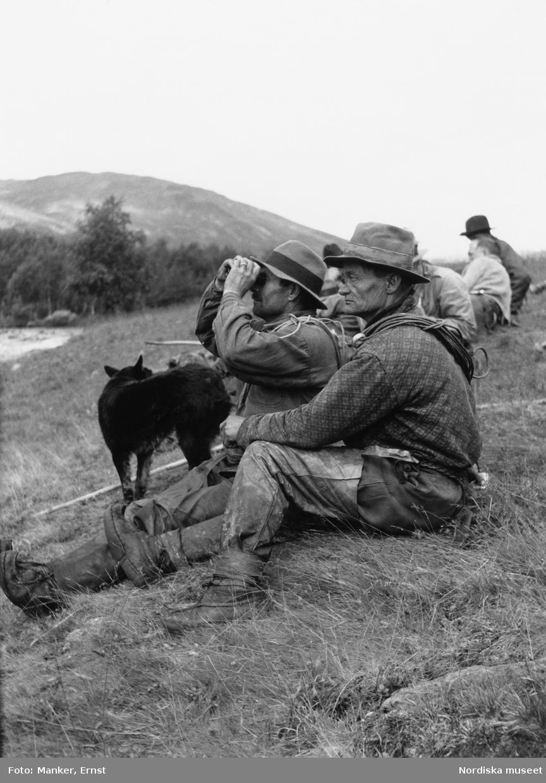 Umfors. Umbysamen Abraham Vinka tittar i en kikare, bredvid honom sitter Nils Andreas Nilsson. Framför männen står en hund.