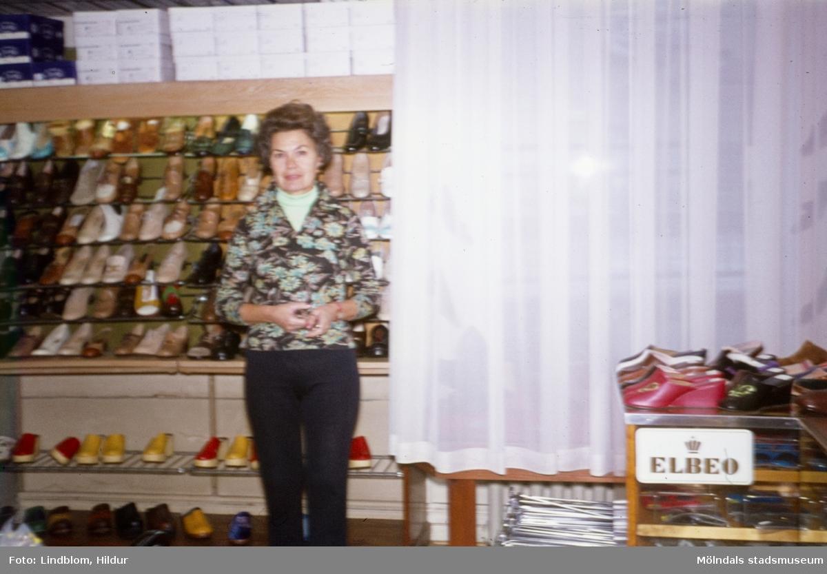 En kvinna fotograferad i Rasmussons skoaffär med adress Kvarnbygatan 4 vid Gamla Torget i Mölndal, 1970-tal.  För mer information om bilden se under tilläggsinformation.