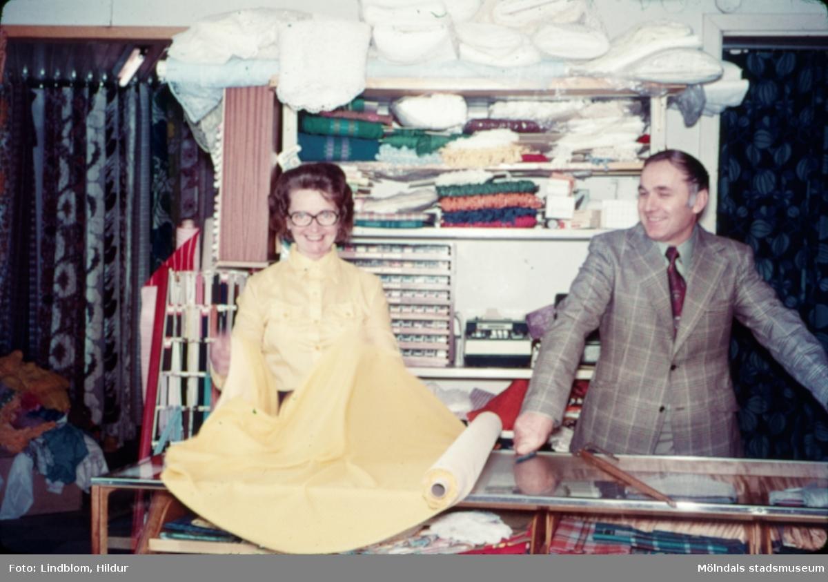 En kvinna och en man fotograferade i en tygaffär, troligtvis vid eller i närheten av Gamla Torget i Mölndal, 1970-tal.  För mer information om bilden se under tilläggsinformation.