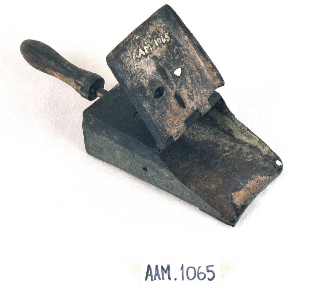 Fyrskuffe av jern med lokk, dreiet håndtak av eik. På kassens lokk og overside en knott omgitt  av 4 huller. Lokket påklinket kassen med  nagler. Under håndtaket lærrem til opphengning.