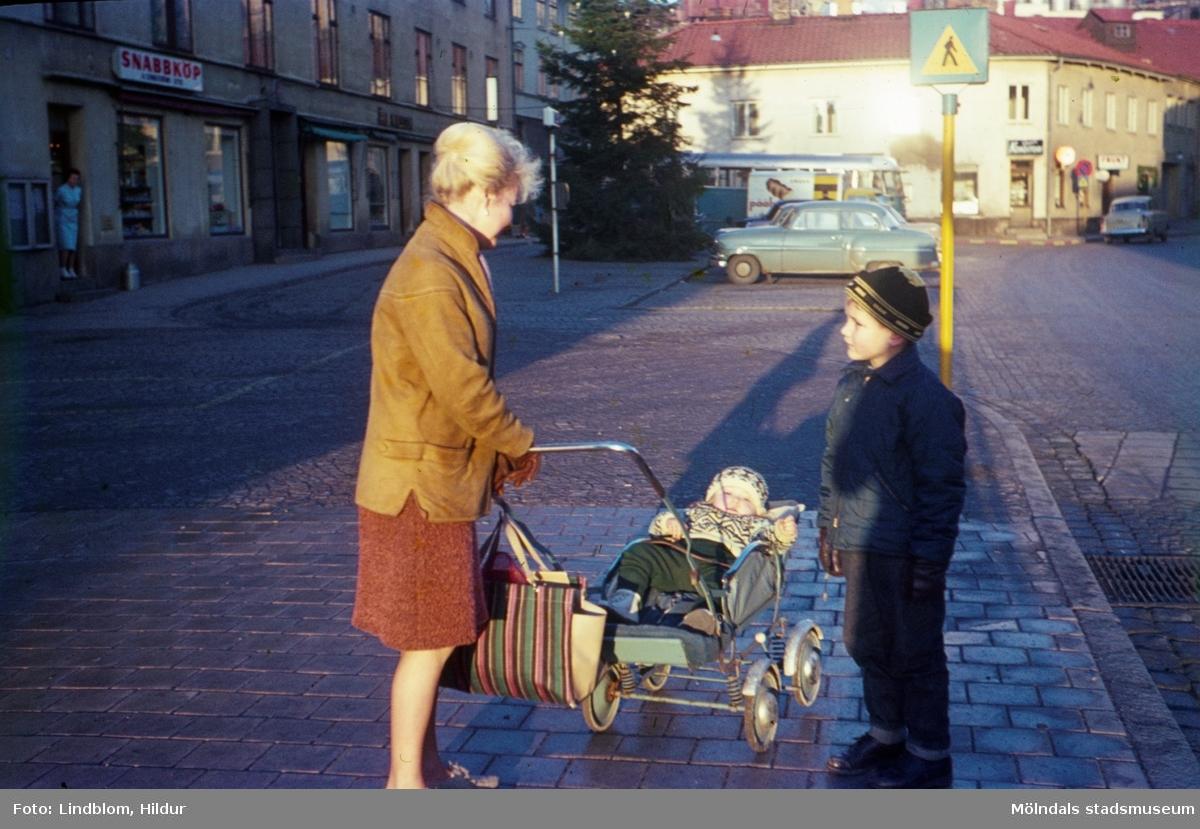 En kvinna med två barn, varav det ena ligger i en barnvagn, står på Gamla Torget i Mölndal, 1960-tal. I bakgrunden till vänster ses huset Kvarnbygatan 43, tidigare Mölndals stadshus, sedermera musikskola. Till höger ses Kvarnbygatan 45.  För mer information om bilden se under tilläggsinformation.