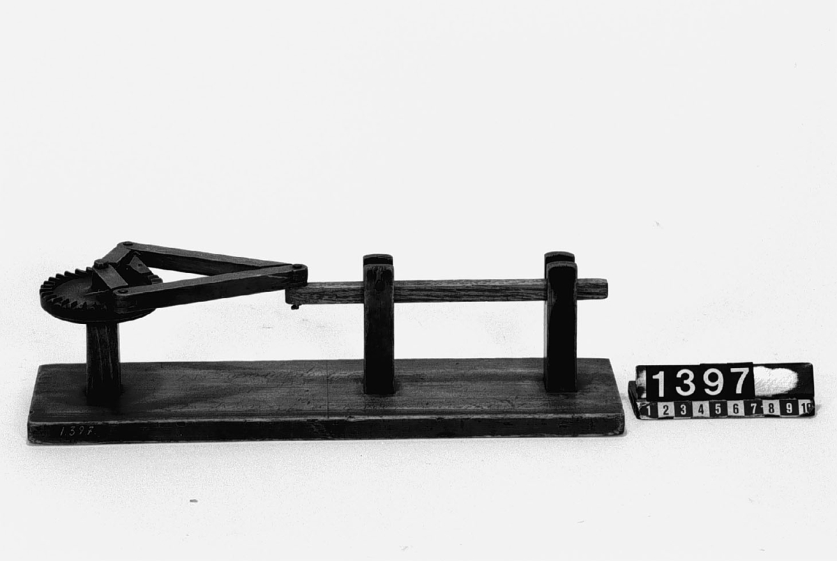 Modell ur Polhems mekaniska alfabet. Text på etikett: (Märkt med en del inskriptioner). Genom en fram- och återgående rörelse hos den långa armen erhålles med hjälp av de ledade ramarna och klaffarna en kontinuerlig rotationsrörelse hos kuggkransen.