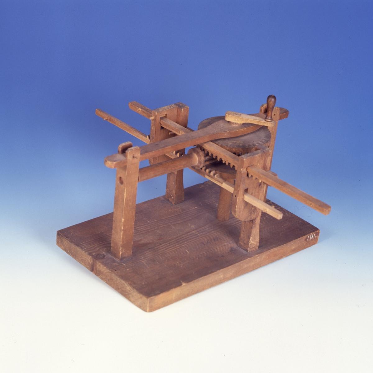 Modell ur Polhems mekaniska alfabet. Text på föremålet: LXXXIII. En roterande rörelse hos de båda halva kuggkransarna överförs med hjälp av ett pinnhjul till en fram- och återgående rörelse hos kuggstängerna.