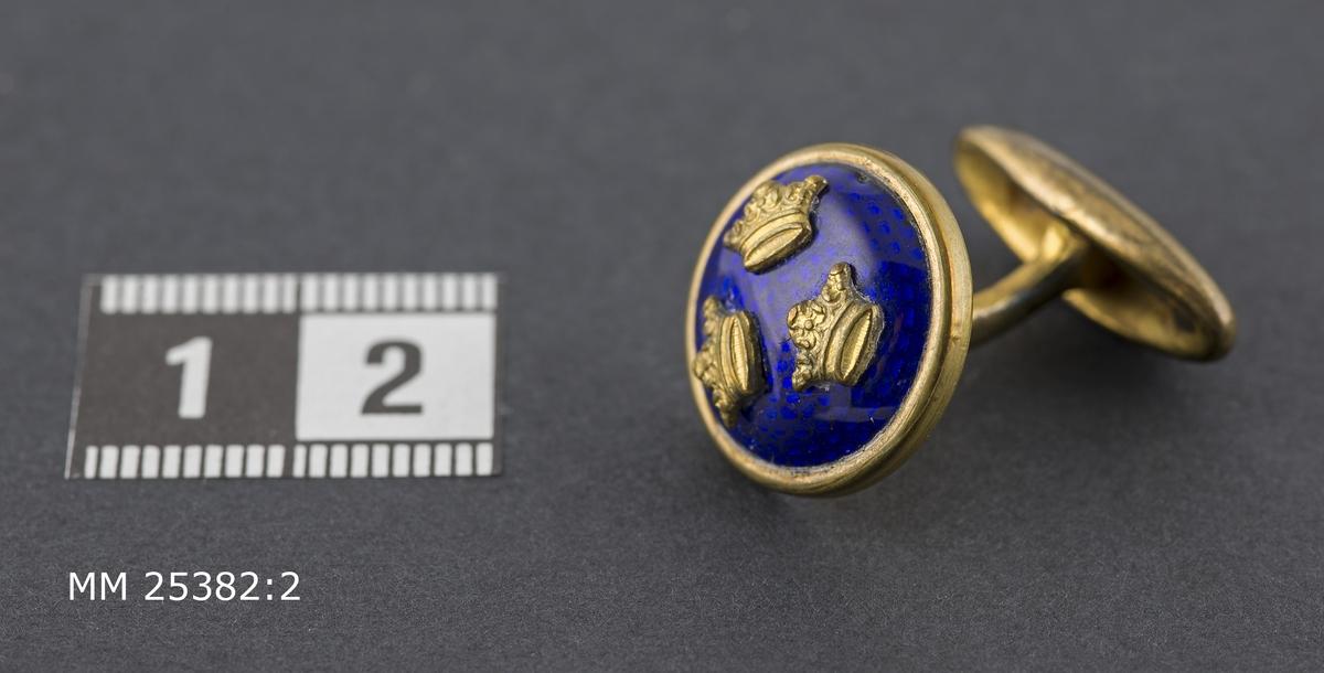 Manschettknapp i gulmetall. Runda med tre kronor i guld på mörkblå emaljerad botten.